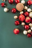 Červené a zlaté vánoční ozdoby / koule na zeleném pozadí. Flat lay, top view Nový rok / Vánoční sváteční kompozice.
