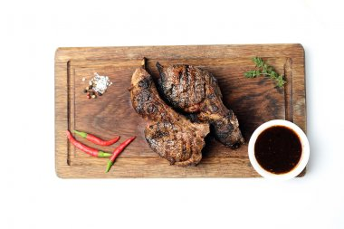 Grilled lamb steaks on cutting board