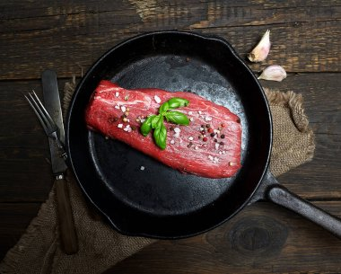 raw veal meat in a frying pan