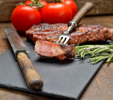grilled steak with rosemary and cutlery