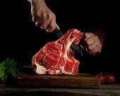 Muž řezání syrové hovězí maso.