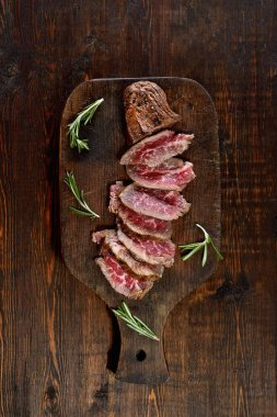 cutting board with grilled steak on wooden background