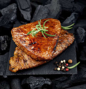 Grilled juicy steak on black board