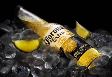 Bottle of original Corona Extra beer with lime slices on ice cubes