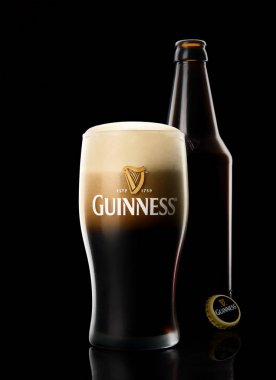 Glass of Guinness original beer with bottle on black background