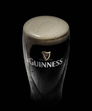 Glass of Guinness original beer on black background
