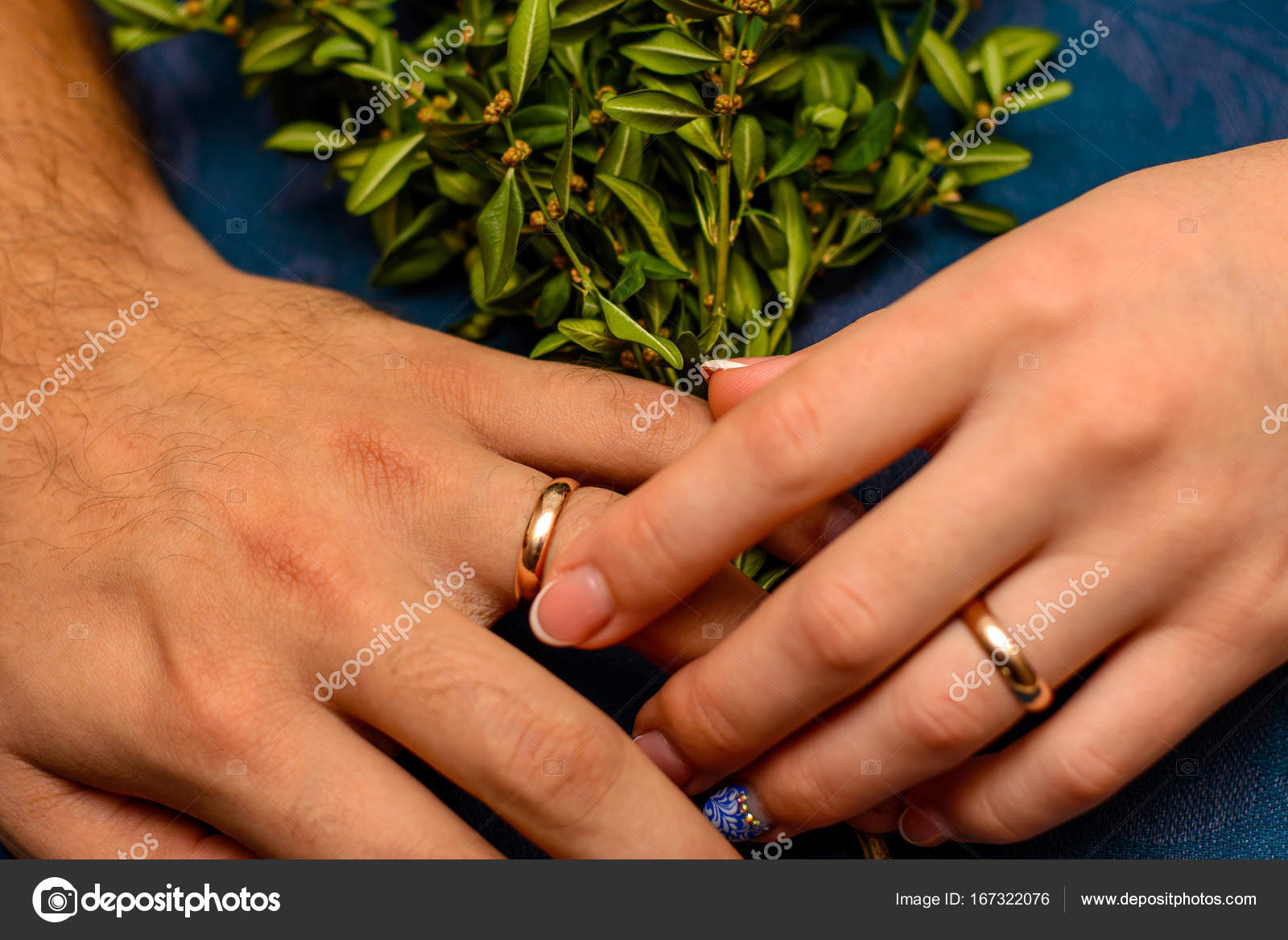 Photo of hands with beautiful wedding rings and green leaves on ...