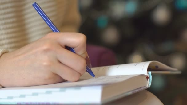 Írni a Jegyzettömb A női kéz a háttérben fény New Years New Years szeretnék írja egy golyóstoll ünnepi karácsonyi kívánságait a notebook