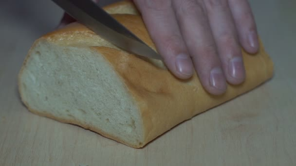 Slicing bread with a knife Bread being sliced then buttered with butter.