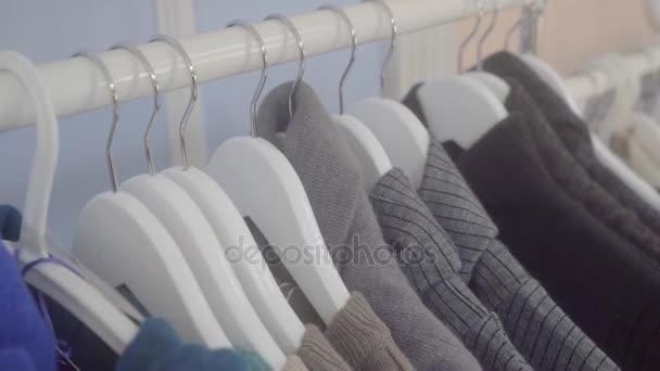 Prodej oblečení v obchodě. Obchod s oblečením. Oblečení jsou uvedeny na prodej v obchodě. Regály pro ukázku oblečení. Pohyb kamery.
