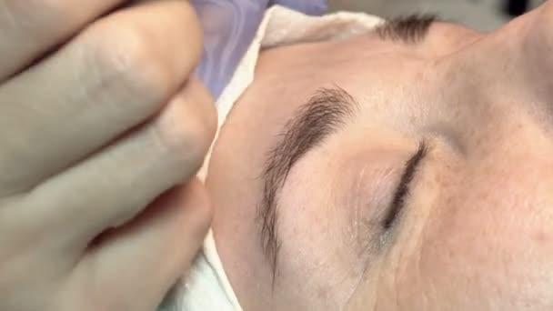 Im Augenbrauen-Schönheitssalon kümmert sich der Meister um die Augenbrauen. Design und Färbung Styling und Laminierung von weiblichen Augenbrauen. Farbabstimmung. Korrektur mit einem kosmetischen Werkzeug.