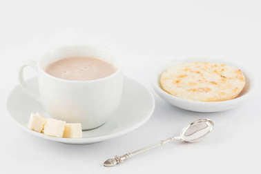 Cup of hot chocolate with cheese and arepa served in white dishw