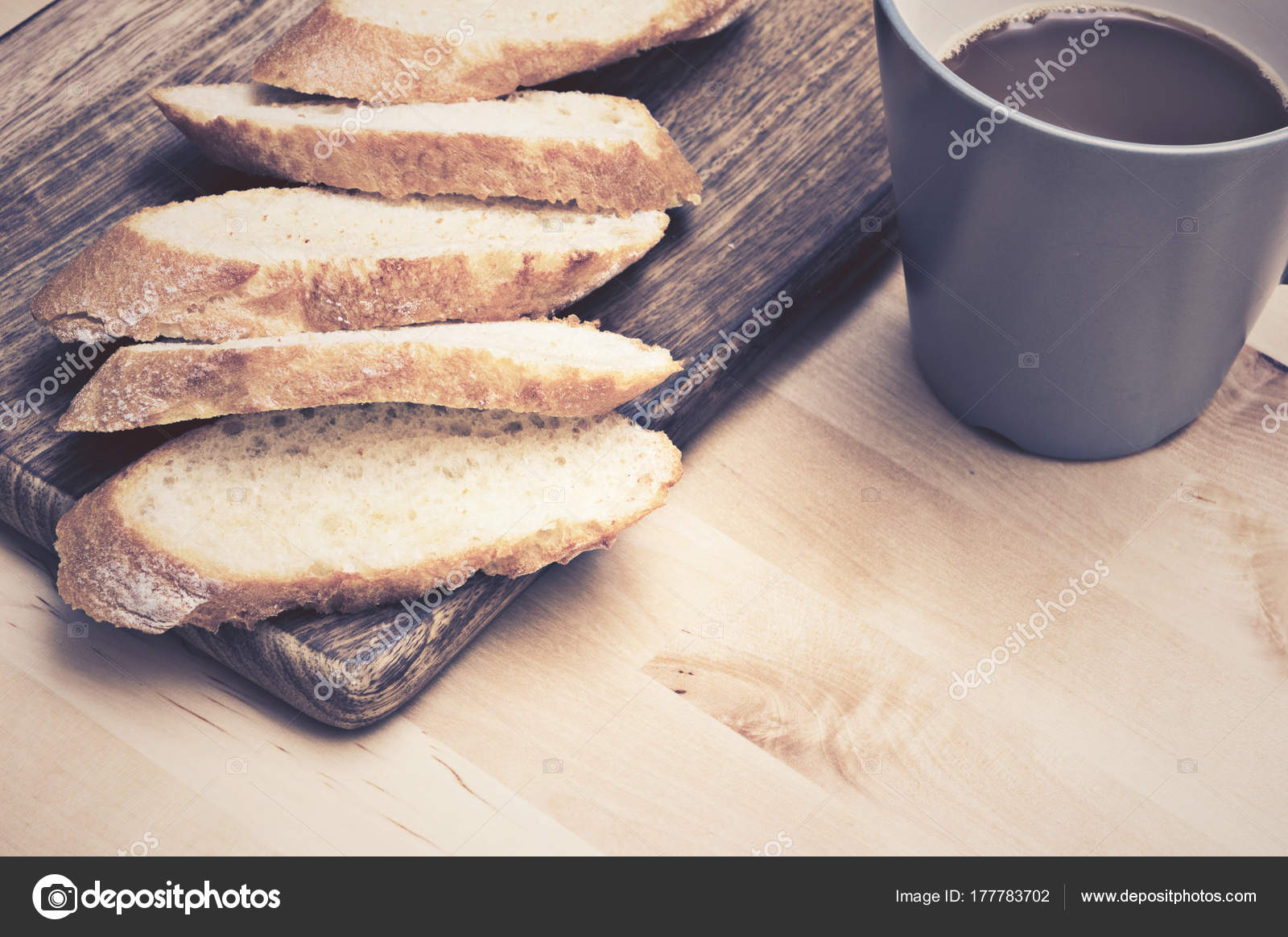Sliced Baguette Bread On Wooden Plate With Coffee Stock Photo