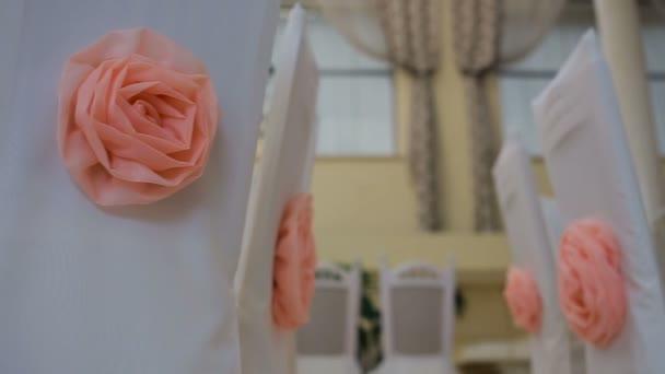Interiér svatební dekorace sál připraven pro hosty. Krásné místo pro svatby a obřady. Pěkná výzdoba s růžové růže na bílé židle