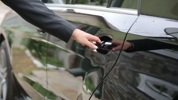 Muž otevře dveře auta v close-up, nastaví v autě a zavře dveře
