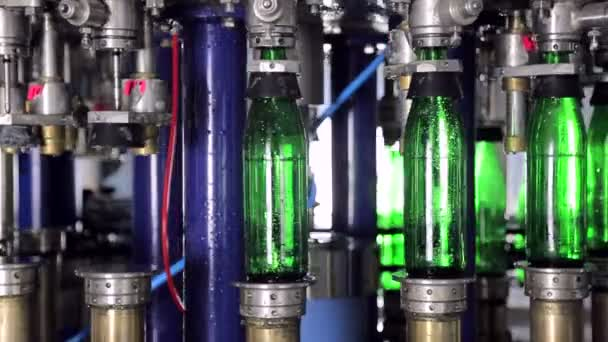 Line of water production. Green glass bottles move automatically along the lines of production, and fill with water