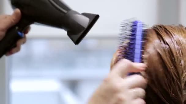 Žena v salonu krásy vysouší vlasy s vysoušečem vlasů
