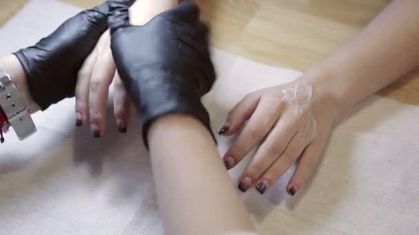 Masáž dlaně v salonu krásy. Masíruje pomalu dlaněmi klienta