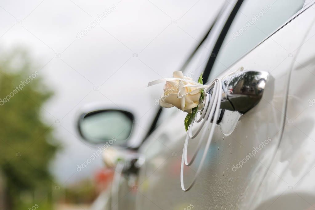 Red and white decorations on the hood of the car. Wedding decorations on a car.