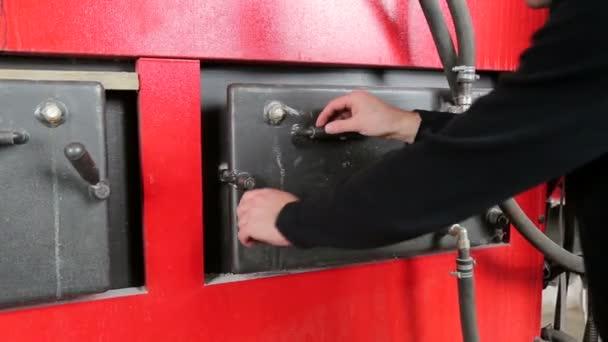 Mann öffnet die Tür von einem Industriekessel. Alternativer Kraftstoff verbrennt in einem Kessel