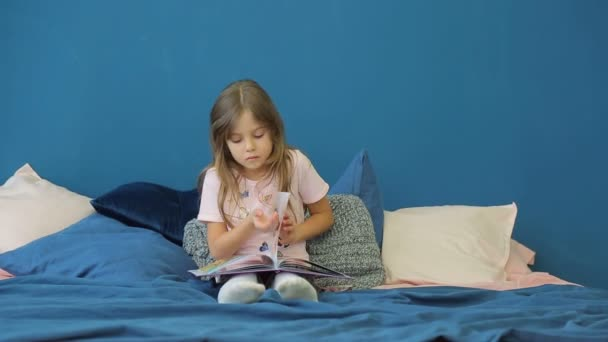 A little girl is reading a book on the bed.