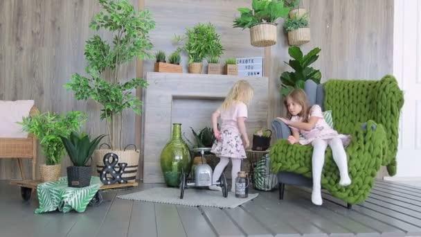 Dvě dívky hrají v místnosti zdobené zelenými rostlinami. Dvě dívky sestry baví