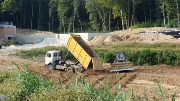 Der Lastwagen schüttet Sand auf das Gelände. Bagger schaufelt Sandkübel.