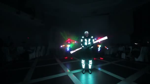 Laser ice show. Artists demonstrate dance and laser show in a dark room. Clothing glows with ice and laser light. Night laser disco.