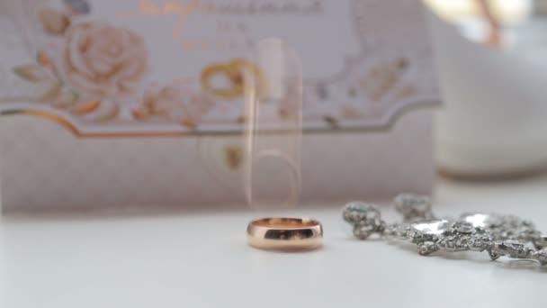 Svatební prsten. Snubní prsten se převalí na jiný a udeří do něj. Svatební pozadí.