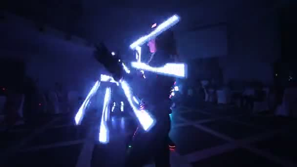 Laser LED show. Artists demonstrate dance and laser show in a dark room. Clothing glows with ice and laser light. Night laser disco.