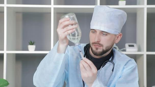 Ärzte betrachten das Gefäß mit dem Medikament. Der Arzt wählt das Medikament aus einem großen Glasgefäß in eine Spritze. Vorbereitung auf die Behandlung.