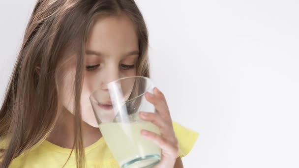 little girl throws a tablet with vitamins that dissolve in water. The girl drinks fizzy medicine.