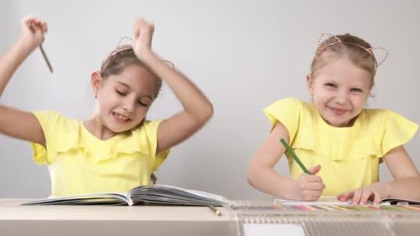 Vtipné a zábavné děti. Děti u stolu tančí a tvoří. Dvě děti sedí u stolu a malují omalovánky.