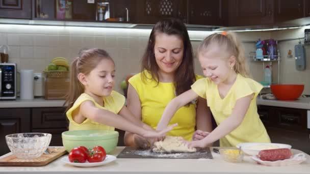 Anya és a két lánya jól érzik magukat a konyhában. Anya megtanítja a gyerekeket pizzát készíteni. Boldog anya és boldog gyerekek együtt főznek vacsorát a konyhában..