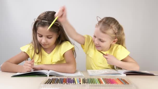 Funny and funny children. Children at the table dance and create. Two children are sitting at a table and coloring a coloring book.