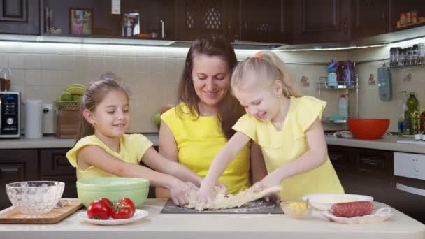 Anya és a gyerekek pizzát főznek a konyhában. A gyerekek segítenek az anyjuknak főzni. Stílusos család öltözött sárga ruhák készül a konyhában
