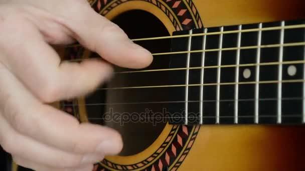 Detailní záběry muže, hraje na akustickou kytaru
