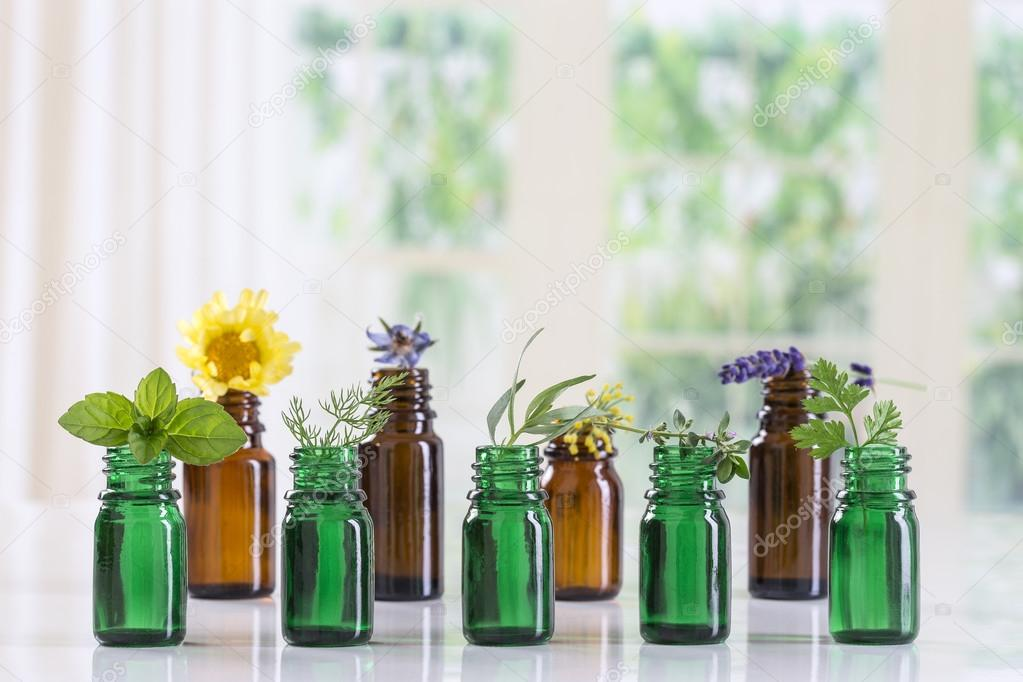 bottle of essential oil with selective medicinal herbs and plants