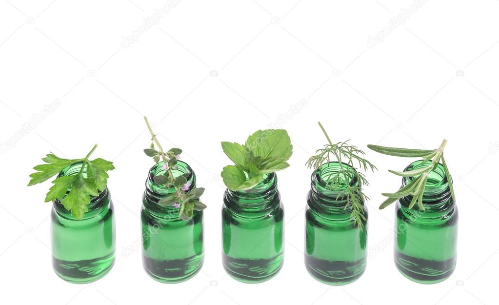 Bottle of essential oil with herb fresh plants and flowers