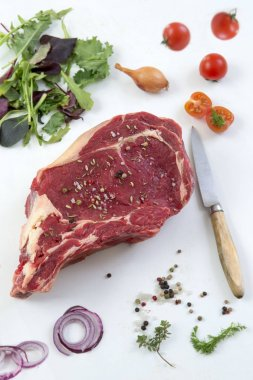 Raw T-bone Steak for grill or BBQ on cutting board with knife over on a white background, top view