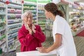 alte Frau mit Halsschmerzen in der Apotheke, die sich von einem Apotheker in der Apotheke beraten lässt