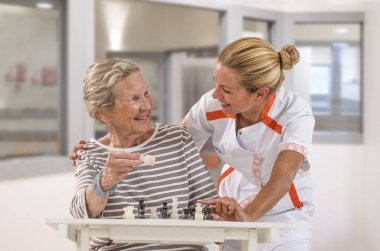 Young homecarer playing chess with elderly woman in getting up in large, windows, background, room
