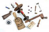 Antique tools for reloading of hunting cartridges, powder measure, cartridge wad tampers, a lot of small bags with lead shots on white background