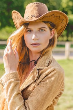 Girl in a cowboy hat looking straight at the camera. Sexy woman with cowboy hat.