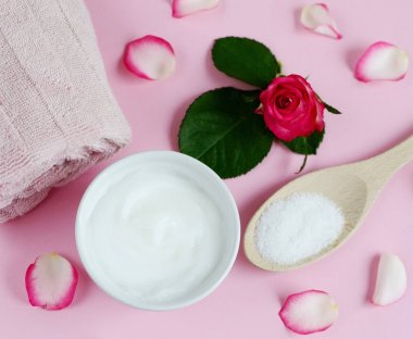 Cosmetic creams and bath towel with pink flowers