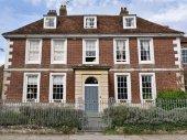 Fotografie Großes Haus außen mit braunen Ziegelmauer, graue Tür und Zaun mit Sträuchern