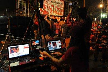 Bangkok - January 29: video editor operating editing system during large city center red-shirt rally