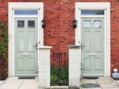 Fotografie Exteriér domu s dvěma dveřmi, plot a keře