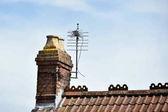 Fotografie Zavřít pohled na střechy s komínem proti modré obloze