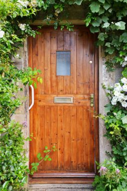 Brown house door with rich plants around